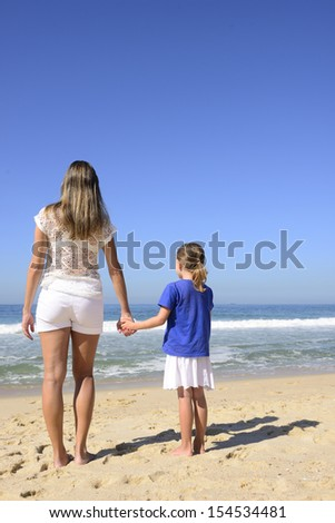 Mother and daughter on the beach holding hands
