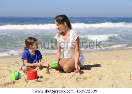 Mother and daughter on the beach playingin the sand