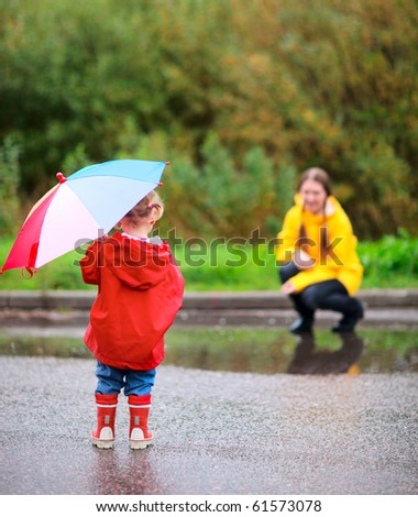 Mother and daughter outdoors at rainy autumn day