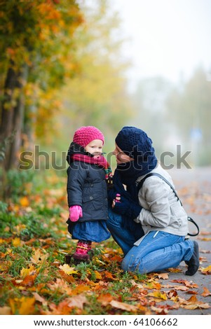 Mother And Daughter Outdoors On Foggy Day