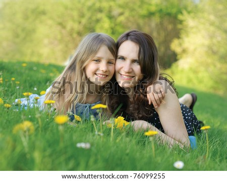 Mother and daughter outdoors on green grass