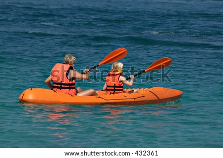 Mother and daughter paddling a kayak on the ocean