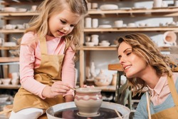mother and daughter painting ceramic pot in pottery workshop