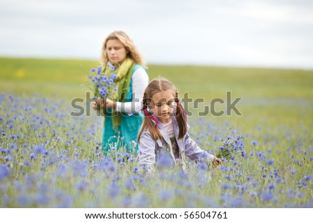 Mother and daughter picking blue flowers in a field