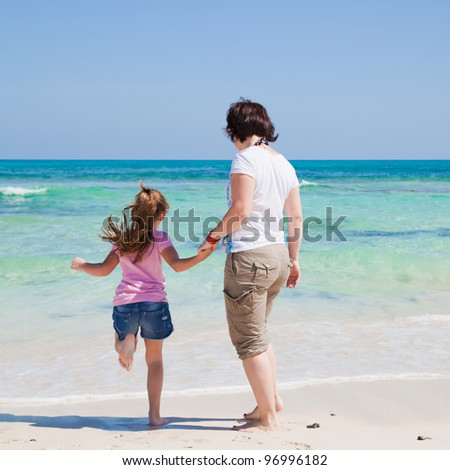 mother and daughter play together by the end of the ocean