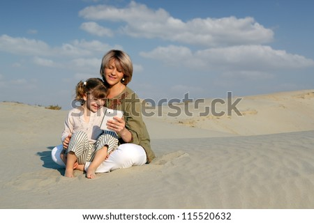 mother and daughter play with tablet in desert