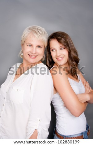 Mother and daughter playfully happy standing back to back