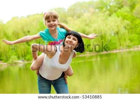 Mother and daughter playing  at the river bank