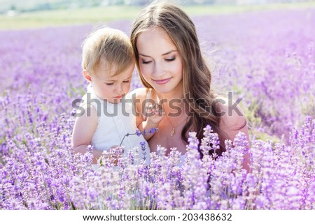 Mother and daughter playing in lavender field on beautiful summer day