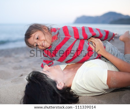 Mother and daughter playing in the beach
