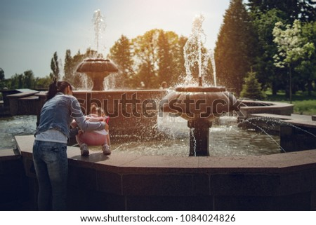Mother and daughter playing in the city square fountain.They sprayed with water.Refreshing on hot summer day.