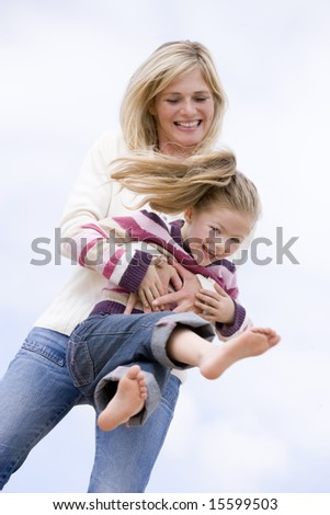 Mother and daughter playing on beach smiling - stock photo