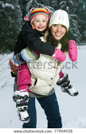 Mother and Daughter playing outside in the snow