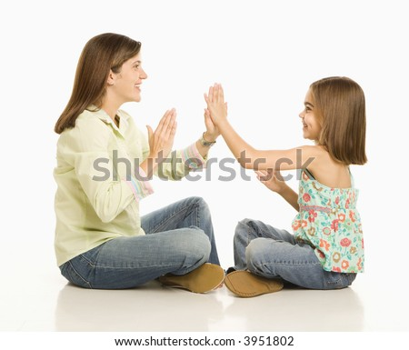 Mother and daughter playing pattyMid adult multiethnic man wearing yellow exercise shirt doing arm curls while looking at bicep.cake.