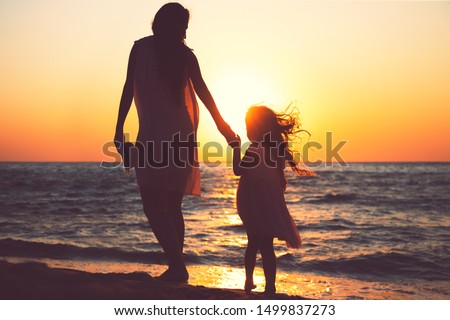 Mother and daughter playing together on the sea beach at sunset.