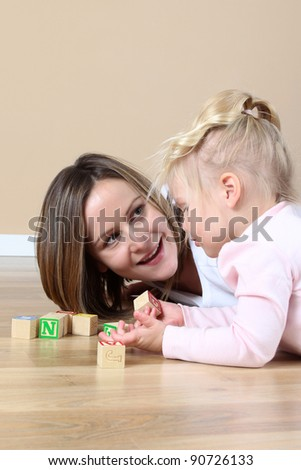 Mother and daughter playing with alphabet building blocks