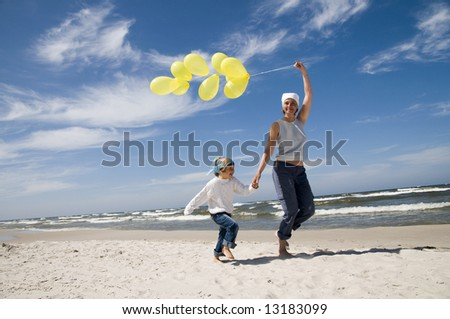 Mother and daughter playing with balloons on the beach
