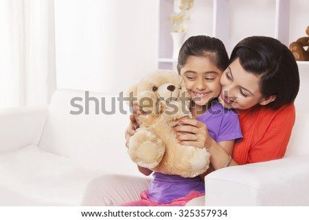 Mother and daughter playing with stuffed toy