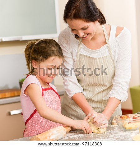 Mother and daughter prepare dough baking apple cake happy together