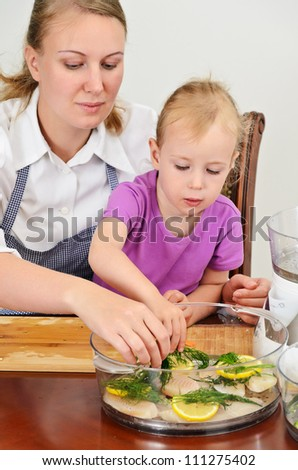 Mother and daughter preparing food in steamer.