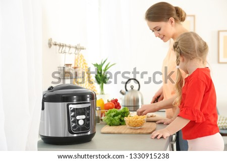 Mother and daughter preparing food near modern multi cooker in kitchen Stock photo ©