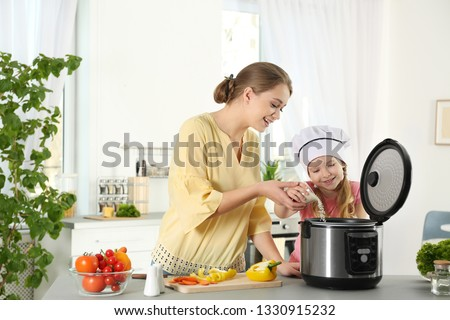 Mother and daughter preparing food with modern multi cooker in kitchen Stock photo ©