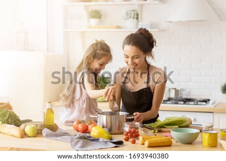 Mother and daughter preparing tasty food at kitchen. Mommy teaching lovely kid to cook. Happy smiling mom and loving child spending time together at home. Healthy meal and dinner preparation