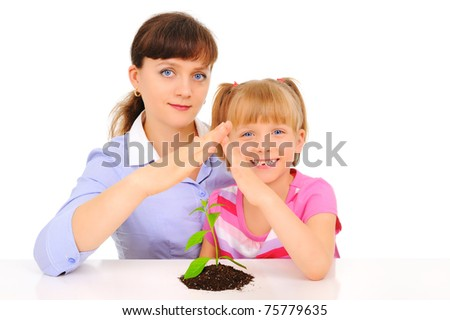 Mother and daughter protecting plant