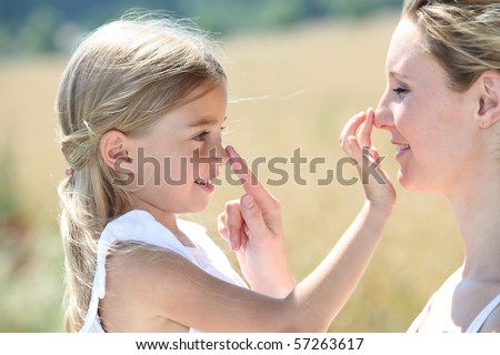 Mother and daughter putting sunscreen on their face - stock photo