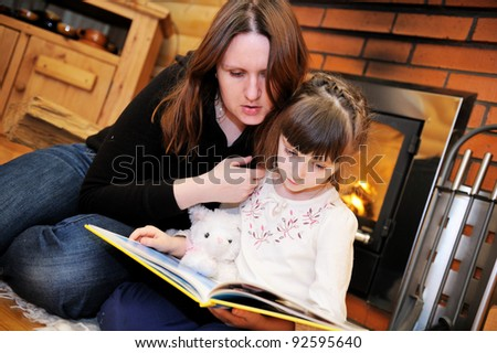 Mother and daughter reading a book in front of fireplace