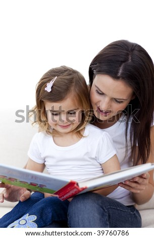 Mother and daughter reading a book on sofa at home