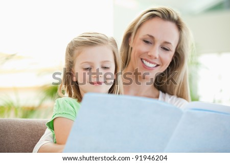 Mother and daughter reading a magazine together on the couch