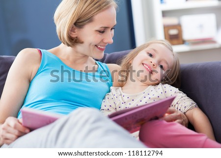 Mother and daughter reading on the couch