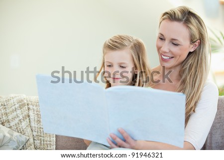 Mother and daughter reading together on the couch