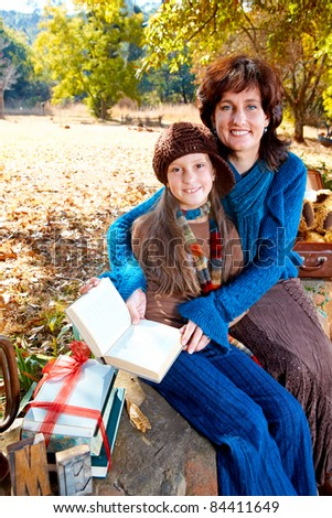 mother and daughter reading vintage books sitting on the wall in the garden on a sunny autumn day