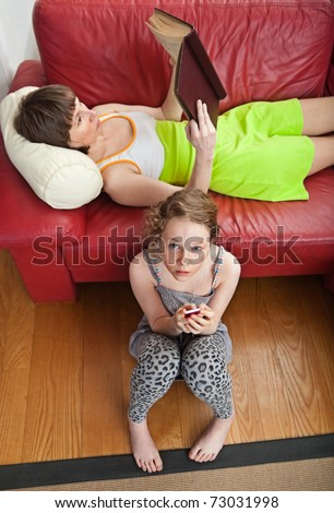 Mother and daughter relaxing at home; high angle view