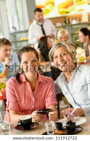 Mother and daughter relaxing in a cafe women restaurant happy