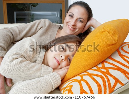 Mother and daughter resting on a white leather sofa at home, smiling.