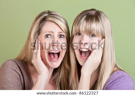 Mother and daughter scream with hands on their faces