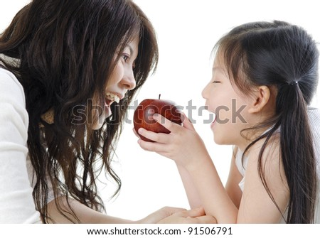 Mother and daughter sharing an apple on white background