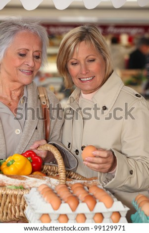Mother and daughter shopping at the market together - stock photo