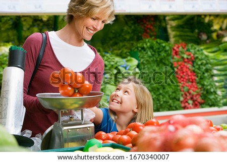 Mother and daughter shopping in supermarket weighing tomatoes