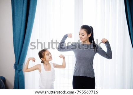 Mother and daughter showing strong hands while working out at home #795569716