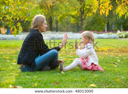 Mother and daughter sit and play in the park
