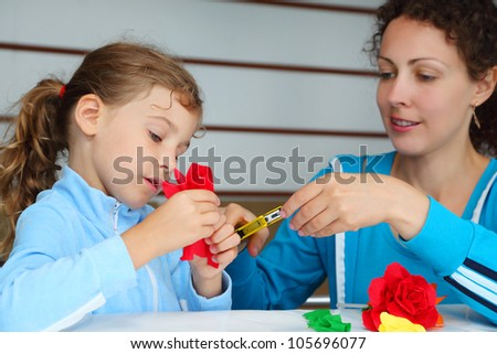 Mother and daughter sit at table and make red artificial roses of tissue paper; focus on girl