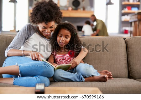 Mother And Daughter Sit On Sofa In Lounge Reading Book Together