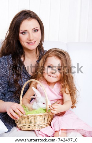 Mother and daughter sit on the sofa and holding basket with Easter bunny