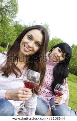 Mother and daughter sitting at a picnic on a blanket drinking wine