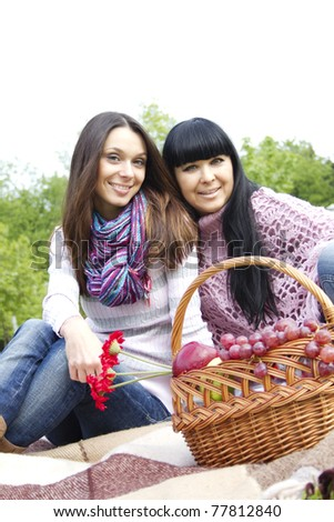 Mother and daughter sitting at a picnic on a blanket next to baskets full of fruit and wine