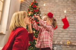Mother and daughter sitting by nicely decorated Christmas tree, having fun at home on Christmas day, trying on Christmas party glasses